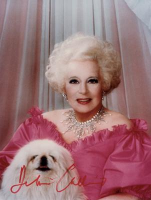 Une photo de Barbara Cartland en rose et avec son petit chien