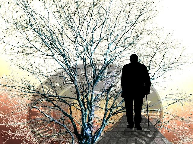Vieil homme qui marche le long d'une avenue avec une canne et qui pense au temps