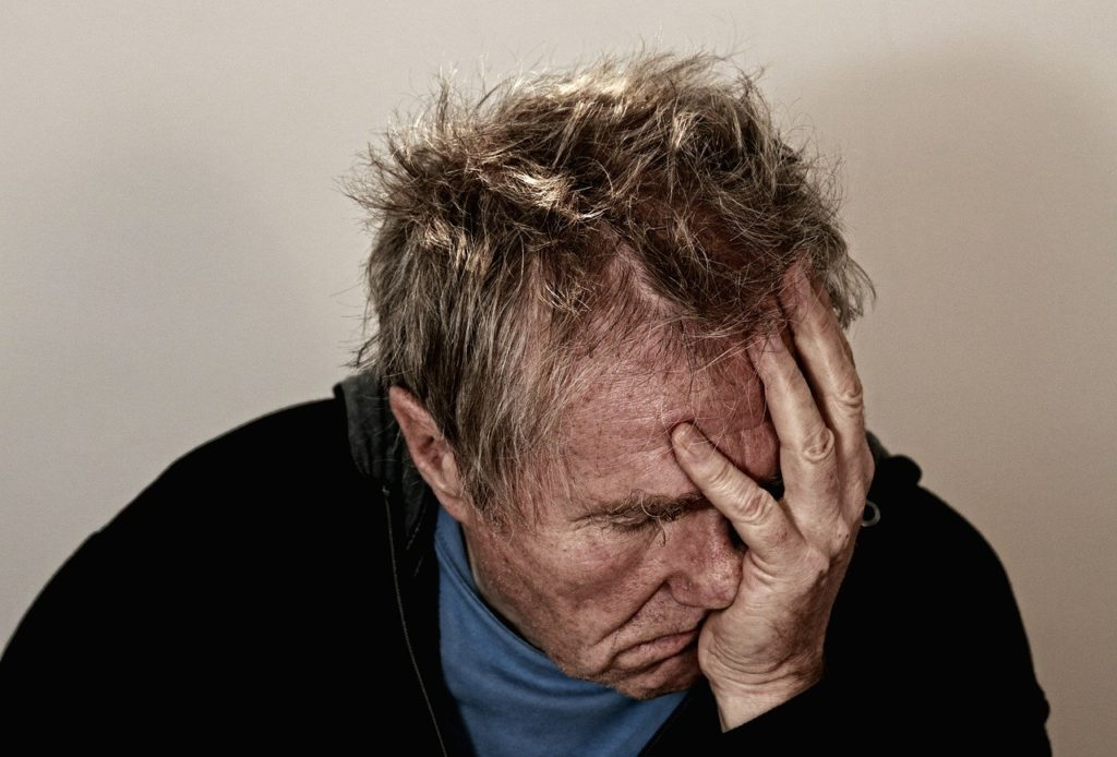Homme qui tient sa tête dans les mains et qui à l'air triste et seul