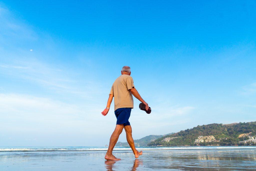 Homme âgé seul qui se balade sur la plage