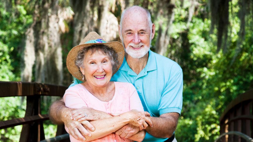 Couple de seniors en vacances assis sur un banc