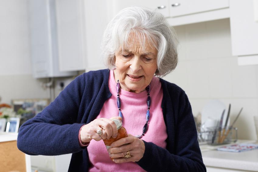 Femme âgée qui a du mal à ouvrir un pot