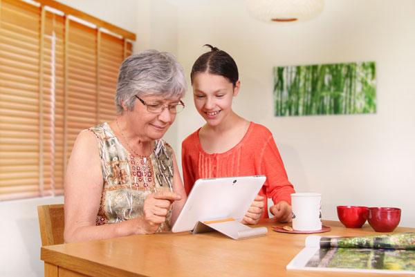 Tablette senior utilisée par grand-mère et petite-fille